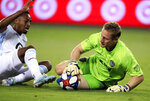 Sporting Kansas City goalkeeper Tim Melia, right, makes a save in front of Minnesota United forward Mason Toye during the first half of an MLS soccer match in Kansas City, Kan., Thursday, Aug. 22, 2019. (AP Photo/Orlin Wagner)