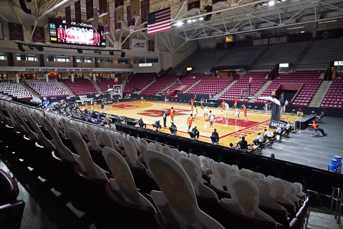 Cardboard cut-out fans sit in seats in a mostly empty arena during the second half of an NCAA college basketball game between Boston College and Syracuse, Saturday, Dec. 12, 2020, in Boston. Syracuse won 101-63. (AP Photo/Elise Amendola)