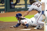 Houston Astros' George Springer, left, scores on a wild pitch as Arizona Diamondbacks starting pitcher Zac Gallen (23) reaches to tag him during the first inning of a baseball game Friday, Sept. 18, 2020, in Houston. (AP Photo/David J. Phillip)