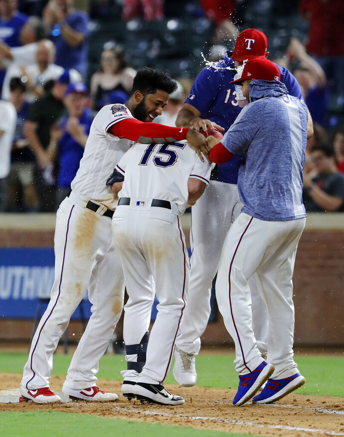 Texas Rangers' Nick Solak (15) is greeted by Elvis Andrus, left, Nomar Mazara, rear, and Jose Trevino, right, after Solak reached first on a fielding error by Los Angeles Angels' Albert Pujols that allowed Delino DeShields to score in the 11th inning of a baseball game in Arlington, Texas, Tuesday, Aug. 20, 2019. The Rangers won 3-2. (AP Photo/Tony Gutierrez)