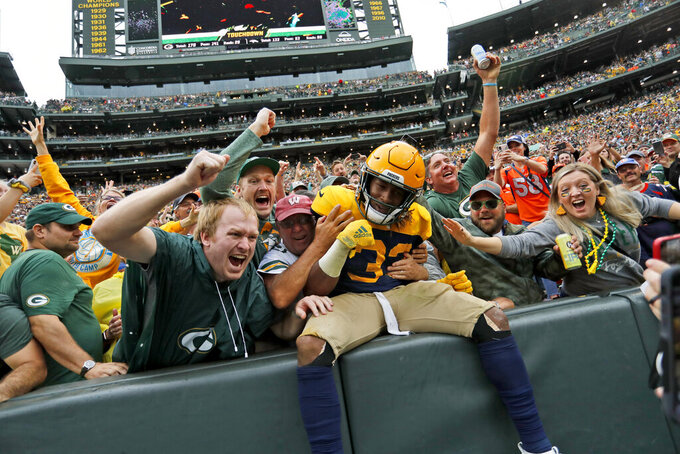 Green Bay Packers running back Aaron Jones is congratulated by fans after scoring during the first half of an NFL football game against the Denver Broncos, Sunday, Sept. 22, 2019, in Green Bay, Wis. (AP Photo/Matt Ludtke)