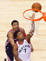 Toronto Raptors guard Kyle Lowry (7) scores past Washington Wizards forward Otto Porter Jr. (22) during the second half of Game 1 of an NBA basketball first-round playoff series in Toronto on Saturday, April 14, 2018. (Nathan Denette/The Canadian Press via AP)