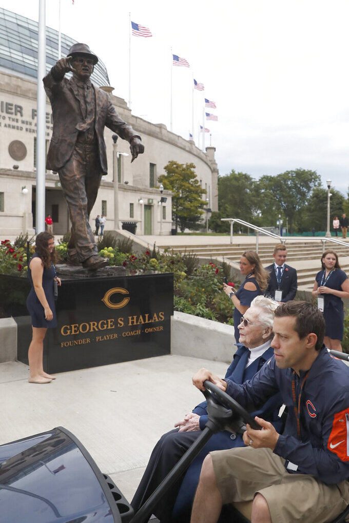 Chicago Bears owner Virginia Halas McCaskey, daughter of Bears' founder George S. Halas, is driven past the newly dedicated statue of her father after an unveiling ceremony outside Soldier Field of statues honoring Halas and Walter Payton Tuesday, Sept. 3, 2019, in Chicago. (AP Photo/Charles Rex Arbogast)