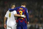 Karim Benzema, izquierda, del Real Madrid, camina junto a Gerard Piqué, del Barcelona, al final del clásico de La Liga en el Camp Nou de Barcelona, el miércoles 18 de dociembre de 2019. (AP Foto/Bernat Armangue)