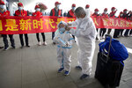 Travelers wearing face masks and suits to protect against the spread of new coronavirus walk past people holding a celebratory banner at Wuhan Tianhe International Airport in Wuhan in central China's Hubei Province, Wednesday, April 8, 2020. Within hours of China lifting an 11-week lockdown on the central city of Wuhan early Wednesday, tens of thousands people had left the city by train and plane alone, according to local media reports. (AP Photo/Ng Han Guan)
