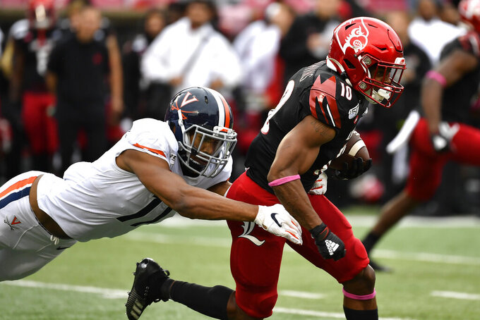 Louisville running back Javian Hawkins (10) is brought down by Virginia linebacker Charles Snowden (11) during the first half of an NCAA college football game in Louisville, Ky., Saturday, Oct. 26, 2019. (AP Photo/Timothy D. Easley)