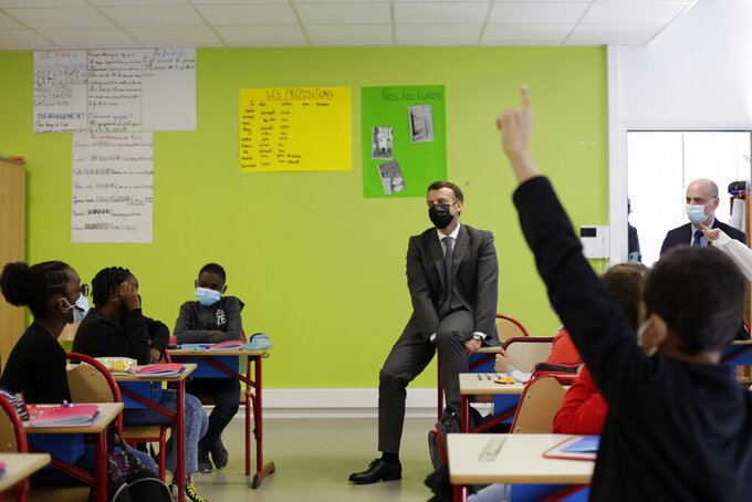 French President Emmanuel Macron talks with pupils during a visit with French Education, Youth and Sports Minister Jean-Michel Blanquer in a school in Melun, south of Paris, Monday, April 26, 2021. Nursery and primary schools reopened on Monday across France after a three-week closure in the first step out of the country's partial lockdown. Meanwhile, high schools students are following online classes. (AP Photo/Thibault Camus, pool)