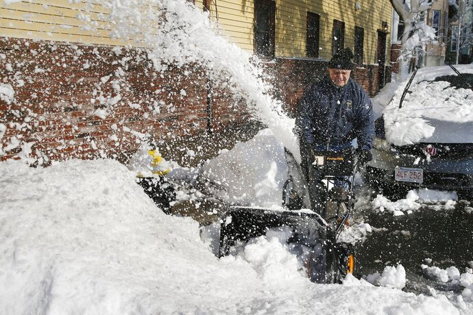 Al Gambale clears snow on Cottage Street in Boston, Wednesday, March 14, 2018. The Boston area was hit with it's third nor'easter of the month on Tuesday, a storm that brought powerful gusts of wind and over a foot of snow. (AP Photo/Michael Dwyer)