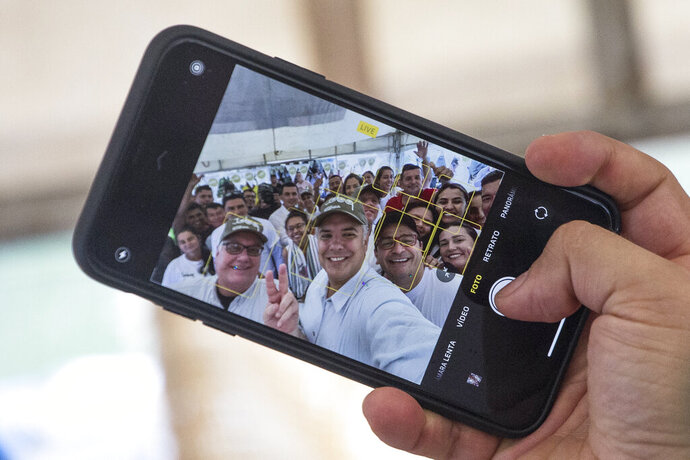 In this Jan. 29, 2020 photo, Colombia's President Ivan Duque, center, takes a selfie with Howard Buffett, left, and cocoa farmers, in La Gabarra, Colombia, Wednesday. The Howard G. Buffett Foundation has committed to spending $200 million over the next few years to transform the impoverished municipality into a model of comprehensive state building. (AP Photo/Ivan Valencia)