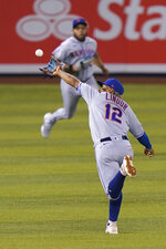 New York Mets shortstop Francisco Lindor (12) catches a ball hit by Miami Marlins' Magneuris Sierra, as left fielder Dominic Smith, rear, backs up the play during the second inning of a baseball game Thursday, Sept. 9, 2021, in Miami. (AP Photo/Wilfredo Lee)