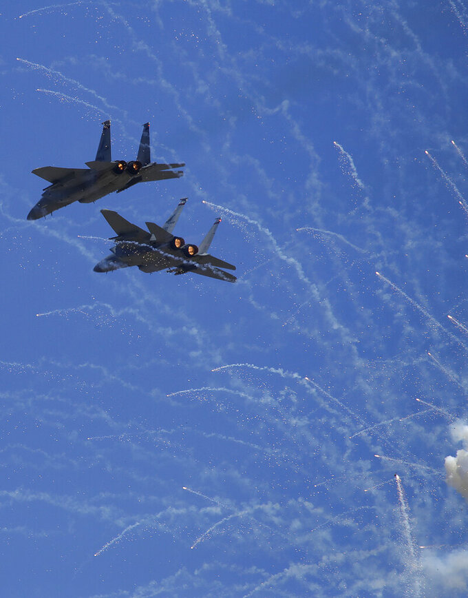 F-15C Eagles from the 123rd Fighter Squadron of the Oregon National Guard fly over fireworks during the national anthem prior to a NASCAR Sprint Cup Series auto race Sunday, June 23, 2019, in Sonoma, Calif. (AP Photo/Ben Margot)