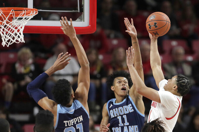 Maryland guard Anthony Cowan Jr., right, goes up to shoot against Rhode Island forward Jacob Toppin, left, and guard Jeff Dowtin during the second half of an NCAA college basketball game, Saturday, Nov. 9, 2019, in College Park, Md. (AP Photo/Julio Cortez)