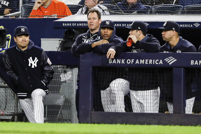 New York Yankees starting pitcher Masahiro Tanaka, of Japan, left, watches with teammates during the ninth inning of the team's baseball game against the Los Angeles Angels on Wednesday, Sept. 18, 2019, in New York. The Angels won 3-2. (AP Photo/Frank Franklin II)