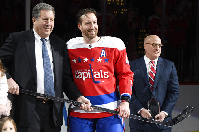 "FILE - In this Jan. 18, 2019, file photo, Washington Capitals defenseman Brooks Orpik, center, poses with Dick Patrick, left, team president, and Bill Daly, deputy NHL commissioner, after he was given a silver stick during a ceremony to honor Opik for playing 1,000 NHL hockey games, before the team's matchup against the New York Islanders in Washington. Orpik has decided to retire after 15 seasons and two Stanley Cup championships. The 38-year-old announced his retirement Tuesday, June 25, 2019. Orpik says his body is ""telling me it is time to move on to something new"" after 1,171 NHL regular-season and playoff games.  (AP Photo/Nick Wass, File)"