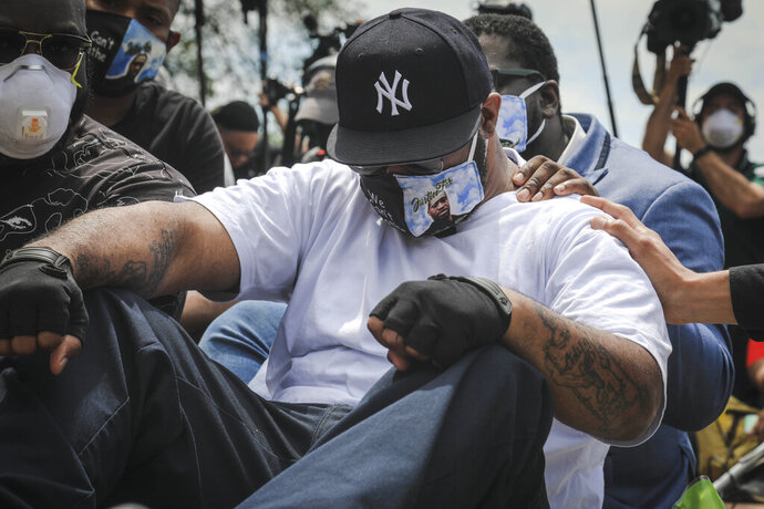 An emotional Terrence Floyd is comforted as he sits at the spot at the intersection of 38th Street and Chicago Avenue, Minneapolis, Minn., where his brother George Floyd, encountered police and died while in their custody, Monday, June 1, 2020. (AP Photo/Bebeto Matthews)