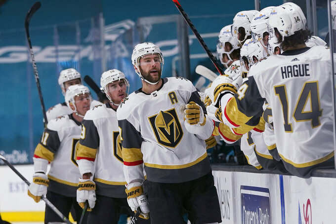 Vegas Golden Knights defenseman Alex Pietrangelo, middle, is congratulated by teammates after scoring against the San Jose Sharks during the first period of an NHL hockey game in San Jose, Calif., Wednesday, May 12, 2021. (AP Photo/Jeff Chiu)