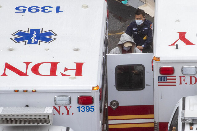 A paramedic transports a patient into the Trauma Center at the Elmhurst Hospital Center, Sunday, March 29, 2020, in the Queens borough of New York. The new coronavirus causes mild or moderate symptoms for most people, but for some, especially older adults and people with existing health problems, it can cause more severe illness or death. (AP Photo/Mary Altaffer)
