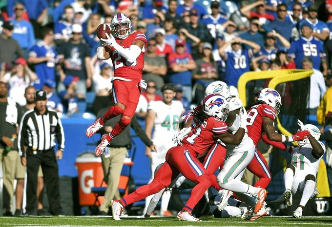 Buffalo Bills safety Micah Hyde, left, soars high to recover an on-side kickoff by the Miami Dolphins, which he ran back for a touchdown in the second half of an NFL football game, Sunday, Oct. 20, 2019, in Orchard Park, N.Y. (AP Photo/Adrian Kraus)
