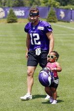 A young fan carries Minnesota Vikings wide receiver Chad Beebe's helmet as he headed to the field during the NFL football team's training camp Friday, July 26, 2019, in Eagan, Minn. (AP Photo/Jim Mone)