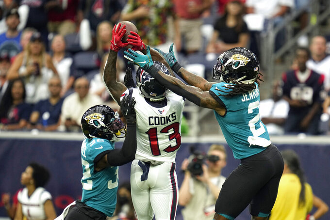 Houston Texans wide receiver Brandin Cooks (13) catches a pass for a first down as Jacksonville Jaguars' Tyson Campbell (32) and Rayshawn Jenkins (2) defend during the first half of an NFL football game Sunday, Sept. 12, 2021, in Houston. (AP Photo/Sam Craft)