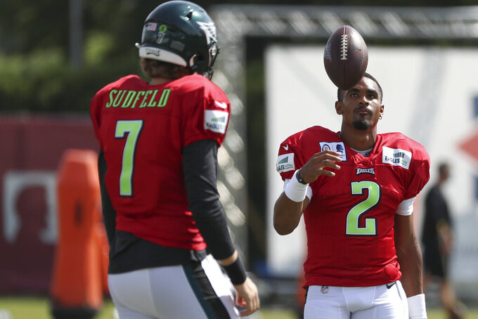 Philadelphia Eagles quarterback Jalen Hurts (2) tosses up the ball next to quarterbacked Nate Sudfeld (7) during an NFL football training camp practice in Philadelphia, Friday, Aug. 21, 2020. (Heather Khalifa/Pool Photo via AP)