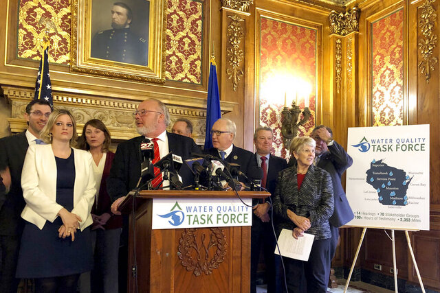 State Rep. Todd Novak, center, gathers members of a bi-partisan water pollution task force in the state Capitol in Madison, Wis., Wednesday, Jan. 8, 2020, to announce recommendations for curbing contamination from manure and fertilizer. The group released its recommendations to reduce contamination after a year's worth of work, releasing 13 bills Wednesday that call for creating a new water policy office, increasing state funding for county conservation workers and increasing grants for well reconstruction or replacements. (AP Photo/Todd Richmond)