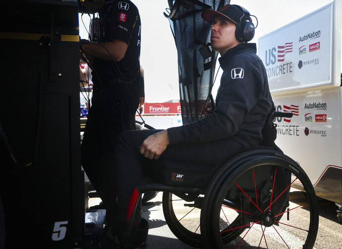 FILE - In this March 8, 2019, file photo Robert Wickens sits in the pit area at the IndyCar Grand Prix of St. Petersburg auto race in St. Petersburg, Fla. Nearly a year after his devastating injury in an IndyCar race, Wickens will indeed get to drive a car again at a race track. He will lead the parade lap Sunday before the Toronto IndyCar race in an Acura NSX equipped with hand controls. (Dirk Shadd/Tampa Bay Times via AP, File)