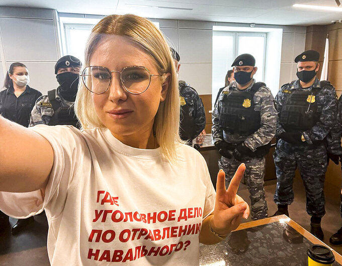 """In this handout photo released by Russian opposition activist Lyubov Sobol in her twitter.com/SobolLubov account, Russian opposition activist Lyubov Sobol wearing in t-short with the words reading """"where is the criminal case for the poisoning of Navalny?"""" makes a selfie in front of Russian Federal Bailiffs service officers in a courtroom in Moscow, Russia, on Thursday, April 15, 2021. Sobol, a top associate of Russia's imprisoned opposition leader Alexei Navalny was convicted of trespassing Thursday and handed a suspended sentence of one year community service after she tried to doorstep an alleged security operative believed to be involved in Navalny's poisoning with a Soviet-era nerve agent. (twitter.com/SobolLubov via AP)"""