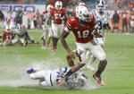 Miami wide receiver Lawrence Cager (18) escapes a tackle by Duke safety Brandon Feamster for a first down during the first half of an NCAA college football game Saturday, Nov. 3, 2018, in Miami Gardens, Fla. (AP Photo/Lynne Sladky)