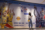 In this Friday, Oct. 11, 2019, photo, a woman wearing a mask stands near promotion boards for a NBA preseason game between Brooklyn Nets and Los Angeles Lakers in Beijing. When Houston Rocket's general manager Daryl Morey tweeted last week in support of anti-government protests in Hong Kong, everything changed for NBA fans in China. A new chant flooded Chinese sports forums: