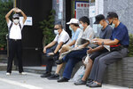 Members of the Nationalist Party, or KMT, wait to cast their ballot for election of its party chairman at a polling station in Taipei, Taiwan, Saturday, Sept. 25, 2021. Fraught relations with neighboring China are dominating Saturday's election for the leader of Taiwan's main opposition Nationalist Party. (AP Photo/Chiang Ying-ying)