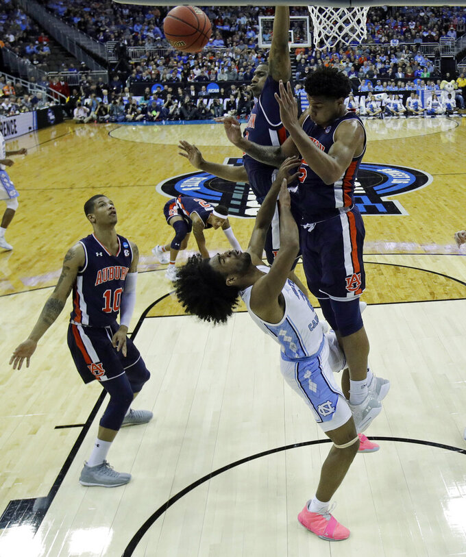 North Carolina's Coby White, center, loses control of the ball as Auburn's Samir Doughty (10) and Chuma Okeke defend during the first half of a men's NCAA tournament college basketball Midwest Regional semifinal game Friday, March 29, 2019, in Kansas City, Mo. (AP Photo/Charlie Riedel)
