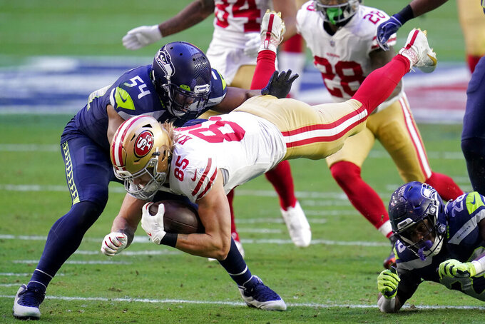 San Francisco 49ers tight end George Kittle (85) is hit by Seattle Seahawks safety Ugo Amadi (28) and middle linebacker Bobby Wagner (54) during the first half of an NFL football game, Sunday, Jan. 3, 2021, in Glendale, Ariz. (AP Photo/Ross D. Franklin)