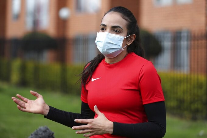 Wearing a face mask, Venezuelan soccer player María Alejandra Peraza, who played last season with Colombia's Millonarios women's team, speaks during an interview in Bogota, Colombia, Thursday, May 21, 2020. Peraza is one of hundreds of professional female players who have received a food package from the Ministry of Sport in Colombia during the lockdown to curb the COVID-19. (AP Photo/Fernando Vergara)