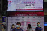 People wearing face masks walk past a bank electronic board showing the Hong Kong share index Tuesday, May 19, 2020.  Asian shares rose Tuesday on optimism about a potential vaccine for the coronavirus after hopes for a U.S. economic recovery in the second half of the year sent Wall Street into a rebound.(AP Photo/Vincent Yu)
