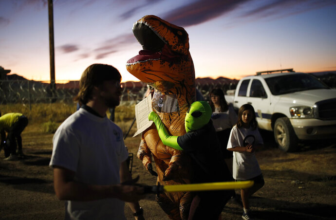 People dressed in costumes visit an entrance to the Nevada Test and Training Range near Area 51, Friday, Sept. 20, 2019, near Rachel, Nev. People came to visit the gate inspired by the