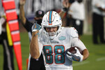 Miami Dolphins tight end Mike Gesicki pumps his fists as he celebrates after scoring a touchdown on a 15-yard pass play against the Jacksonville Jaguars during the first half of an NFL football game, Thursday, Sept. 24, 2020, in Jacksonville, Fla. (AP Photo/Stephen B. Morton)