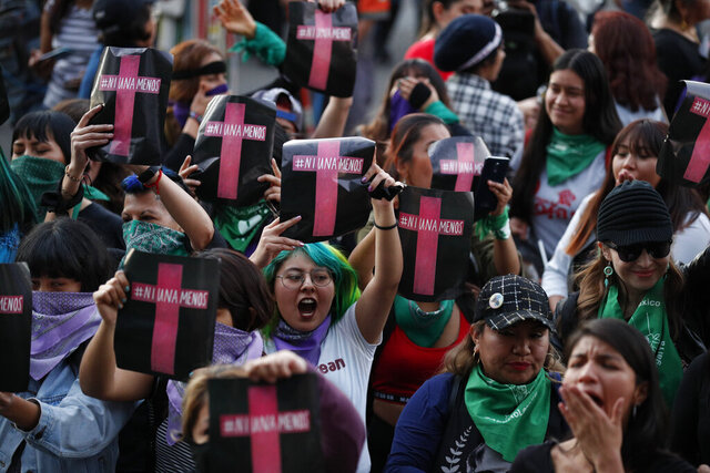 Women hold signs reading in Spanish,