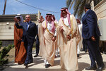 FILE - In this April 4, 2019 file photo, Saudi Minister of Commerce and Investment, Majid bin Abdullah Al Qasabi, center, and Iraq Foreign Minister Mohamed Alhakim, second left, wave as they arrive for the opening ceremony of a Saudi Arabia consulate in Baghdad, Iraq. A flurry of recent diplomatic activity and high-profile visits to the Iraqi capital, points to a new era of openness as the nation sheds its war image. Iraq needs much help and investment to rebuild its cities -- something it can only get from oil- and gas-rich Gulf countries, including Saudi Arabia. (AP Photo/Hadi Mizban, File)