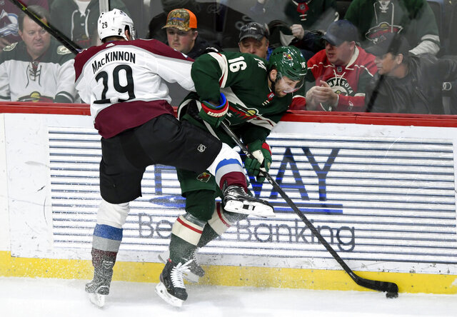 Colorado Avalanche's Nathan MacKinnon (29) pins Minnesota Wild's Jason Zucker (16) to the boards during the third period of an NHL hockey game Sunday, Feb. 9, 2020, in St. Paul, Minn. The Avalanche won 3-2. (AP Photo/Hannah Foslien)