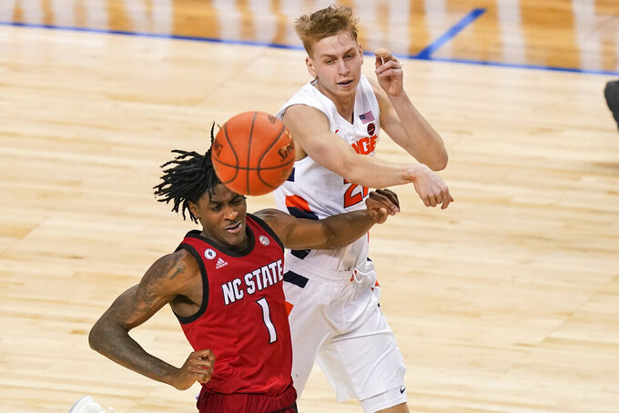 Syracuse forward Marek Dolezaj (21) passes the ball over North Carolina State guard Dereon Seabron (1) during the second half of an NCAA college basketball game in the second round of the Atlantic Coast Conference tournament in Greensboro, N.C., Wednesday, March 10, 2021. (AP Photo/Gerry Broome)