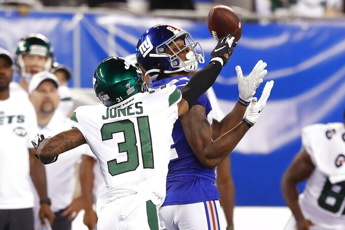 New York Giants wide receiver Alonzo Russell catches a pass in front of New York Jets' Derrick Jones (31) during the first half of a preseason NFL football game Thursday, Aug. 8, 2019, in East Rutherford, N.J. (AP Photo/Michael Owens)
