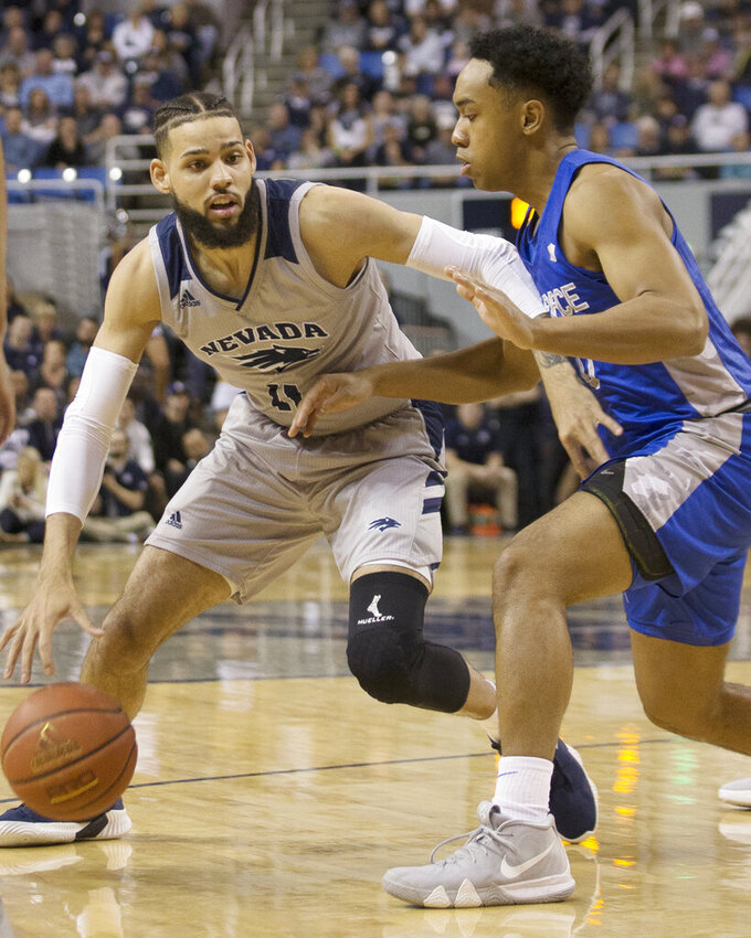 Nevada forward Cody Martin (11) drives past Air Force forward Ryan Swan (34) in the first half of an NCAA college basketball game in Reno, Nev., Saturday, Jan. 19, 2019. (AP Photo/Tom R. Smedes)