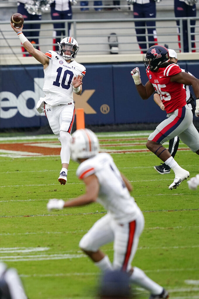 Auburn quarterback Bo Nix (10) passes to wide receiver Anthony Schwartz (1) while under pressure by a Mississippi defender during the first half of an NCAA college football game in Oxford, Miss., Saturday Oct. 24, 2020. (AP Photo/Rogelio V. Solis)