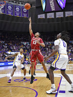 As LSU guard Marlon Taylor (14) and LSU forward Naz Reid (0) watch, Arkansas guard Mason Jones (13) puts the ball up for the go-ahead basket with seconds remaining in an NCAA college basketball game Saturday, Feb. 2, 2019, in Baton Rouge, La. Arkansas won 90-89. (AP Photo/Bill Feig)