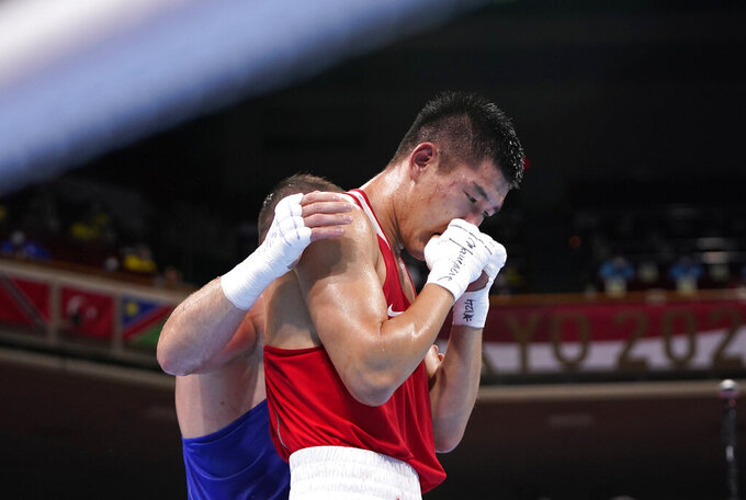 Russian Olympic Committee's Imam Khataev comforts Kazakhstan's Bekzad Nurdauletov after the former won the men's light heavyweight 81-kg preliminaries boxing match at the 2020 Summer Olympics, Wednesday, July 28, 2021, in Tokyo, Japan. (AP Photo/Frank Franklin II, Pool)