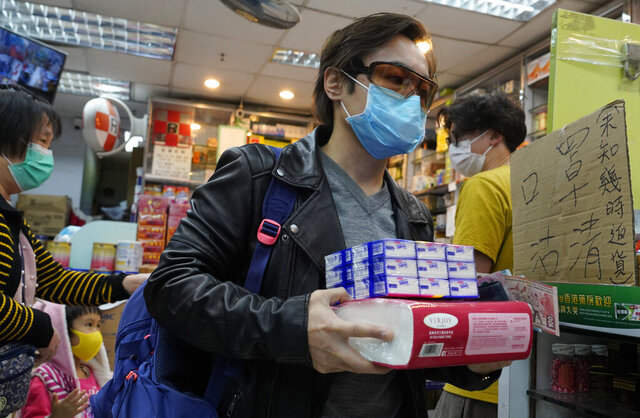 A man wearing a protective face mask carries purchased tissue papers at a pharmacy in Hong Kong, Thursday, Feb. 6, 2020. Ten more people were sickened with a new virus aboard one of two quarantined cruise ships with some 5,400 passengers and crew aboard, health officials in Japan said Thursday, as China reported 73 more deaths and announced that the first group of patients were expected to start taking a new antiviral drug. (AP Photo/Vincent Yu)