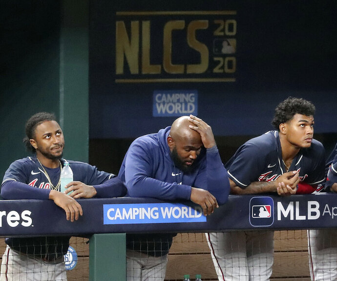 From left to right, Atlanta Braves' Ozzie Albies, Marcell Ozuna and Cristian Pache react to falling to the Los Angeles Dodgers during the ninth inning of Game 6 of the National League Championship Series, Saturday, Oct. 17, 2020, in Arlington, Texas. (Curtis Compton/Atlanta Journal-Constitution via AP)
