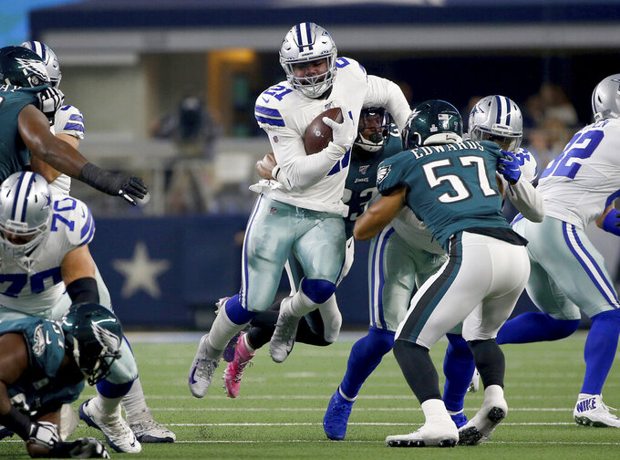 Dallas Cowboys running back Ezekiel Elliott (21) runs the ball as Philadelphia Eagles linebacker T.J. Edwards (57) attempts to make the stop in the first half of an NFL football game in Arlington, Texas, Sunday, Oct. 20, 2019. (AP Photo/Ron Jenkins)