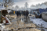 Migrants gather at the Vucjak refugee camp outside Bihac, northwestern Bosnia, Tuesday, Dec. 3, 2019. A European human rights official has demanded immediate closure of a migrant camp in Bosnia where hundreds of people have started refusing food and water to protest dismal living conditions as wintry weather sets in. (AP Photo/Darko Bandic)